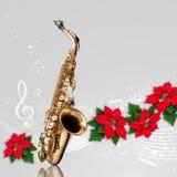 Saxofon med den röda prydnaden för julstjärnablommajul arkivfoton