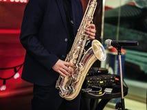 Saxofone do ouro com as salpicaduras nele nas mãos masculinas no backgr vermelho foto de stock royalty free