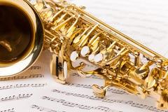 Saxofone dourado bonito do alto em notas musicais Foto de Stock