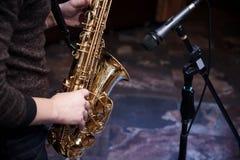 Saxofone dourado nas mãos de um músico imagens de stock royalty free