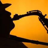 Saxofone Performae que eu mostro em silhueta no ouro Imagem de Stock