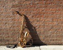 Saxofone que inclina-se contra uma parede de tijolo vermelho Fotografia de Stock Royalty Free