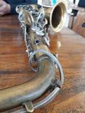 Saxofonen vilar på ett trä royaltyfri bild