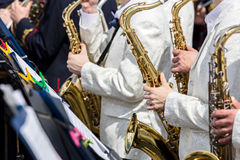 Saxofoner i händer av orkestermusiker under gatakonsert Arkivbilder
