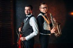 Saxofonist med saxofonen och violinst med fiolduett Arkivbilder