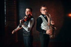 Saxofonist och violinst som spelar klassisk melodi Arkivbilder