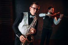 Saxofonist och violinst som spelar klassisk melodi Arkivfoto