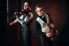 Saxofonist och violinst som spelar klassisk melodi Arkivbild