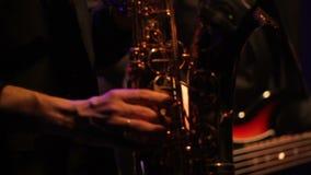 Saxofonist Playing op Gouden Saxofoon bij het Avondoverleg in Zwart Jasje stock videobeelden