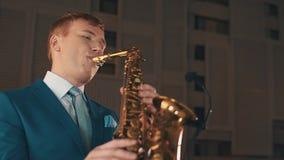 Saxofonista no jazz azul do jogo do terno no saxofone dourado na fase elegance filme