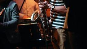 Saxofonisten och trumpetaren med andra musiker utför på aftonen i en jazzstång stock video