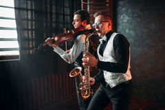 Saxofonman- och fifflareduett som spelar klassisk melodi Arkivfoto