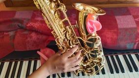 Saxofoon op de piano stock foto's