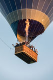 Saxon, Germany - August 13, 2017. Hot air balloon in sky and people in the basket fly over the landscape Royalty Free Stock Images