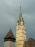 Saxon tower clock closeup in Medias, Romania, on dark sky and cl. Medieval German Lutheran church of Medias, detail of the clock tower, Medias, Romania Royalty Free Stock Photos