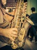 Saxophon in den Händen auf städtischer Straße Lizenzfreie Stockfotos