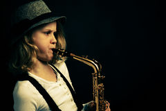 Saxophon performer. Young girl playing saxophone on dark background Stock Image
