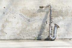 Saxophon vor einer Weinlesewand Stockbilder
