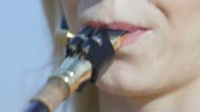 Saxophone παιχνιδιών γυναικών Παιχνίδι κοριτσιών στο goldy σκεπάρνι Ο θηλυκός μουσικός αποδίδει με το σκεπάρνι στην έρημο φιλμ μικρού μήκους