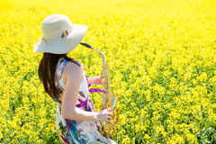 Saxophone παιχνιδιού γυναικών στον τομέα συναπόσπορων Στοκ Εικόνα