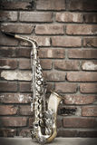 Saxophone Brick Wall. Lone old saxophone leans against brick wall outside abandoned jazz club Royalty Free Stock Image
