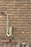 Saxophone Brick Wall. Lone old saxophone leans against brick wall outside abandoned jazz club Royalty Free Stock Photography