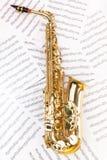 Saxophone brillant d'alto dans la pleine taille sur les notes musicales Photos stock