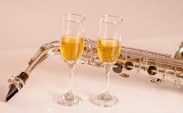 Saxophone brillant se trouvant sur la surface blanche, le papier de notes musicales et deux verres de champagne se reposant à côt Images stock