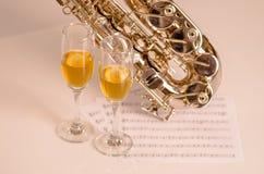 Saxophone brillant se trouvant sur la surface blanche, le papier de notes musicales et deux verres de champagne se reposant à côt Photos libres de droits