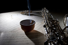 Saxophone cigarette and old sheet music Stock Photos
