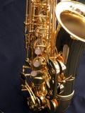 Saxophone detail on black background. Shiny golden saxophone on black background Royalty Free Stock Images