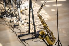 Saxophone of golden color stands on the rack on the stage stock image
