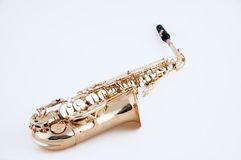 Saxophone Isolated On White Bk. An alto saxophone isolated against a hig key white background in the horizontal view Stock Photos