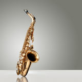 Saxophone Jazz instrument. Alto Saxophone woodwind instrument over gray neutral background Stock Photos