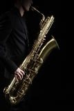 Saxophone Jazz Instruments. Saxophone Jazz Music Instruments Saxophonist with Baritone Sax player isolated on black Royalty Free Stock Photos