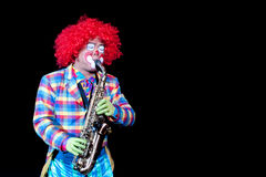 Saxophone Joker. Captured from a show in chimelong cirus  that a joker with Saxophone and isolated in blackground Royalty Free Stock Photography
