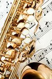 Saxophone keys closeup. With score notes in background Royalty Free Stock Photo