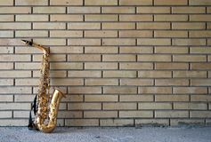 Saxophone leaning against a yellow brick wall Stock Photos