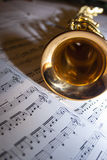 A saxophone lying on sheet music. A soprano saxophone lying on sheet music Royalty Free Stock Photos