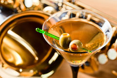Saxophone and martini with green olives Royalty Free Stock Images