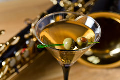 Saxophone and martini with green olives Stock Photos
