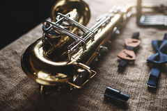 Saxophone, mouthpieces and bowtie, sack background Stock Image