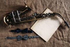 Saxophone, notes and bowtie on canvas background Royalty Free Stock Photo
