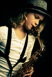 Saxophone performer. Young girl playing saxophone on dark background Stock Photography