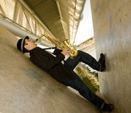 Saxophone Player. A young man with a saxaphone outdoors in an industrial setting Royalty Free Stock Images