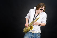 Saxophone player. A musician in a white shirt jamming away on a saxophone, improvising Stock Image