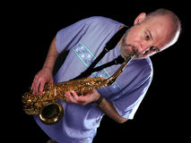 The saxophone player. Man playing saxophone, black background, lateral light, diagonal composition Stock Photography