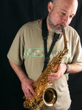 The saxophone player. Man playing saxophone, black background, lateral light Stock Photography