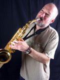 The saxophone player. Man playing saxophone, black background, lateral light Stock Image