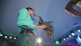 Saxophone player performs on stage with professional light. Close up wide angle stock video footage